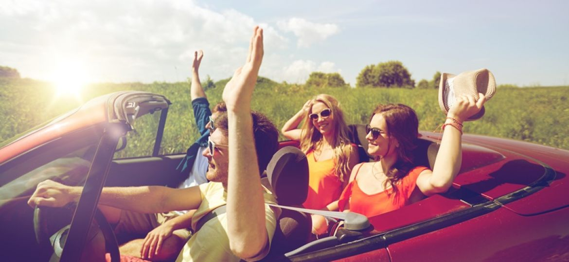 happy friends driving in cabriolet car at country